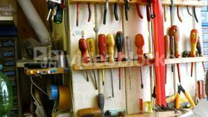 Horologists workshop with clock repairing tools and equipments on wall