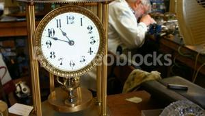Vintage torsion pendulum clock on table while horologist working in background