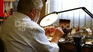 Rear view of horologist repairing a watch