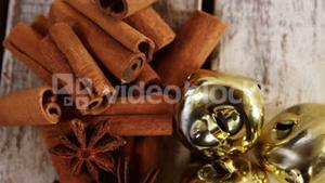 Star anise, cinnamon and jingle bells on a plank
