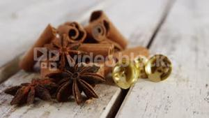 Star anise, cinnamon and small bells on a plank