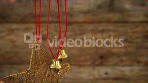 Star shape and small bells ornament hanging on a branch