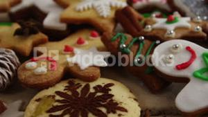 Various christmas cookies and cinnamon on a plank