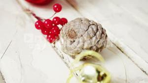 Pine cone, cherries and jingle bell arranged on a plank