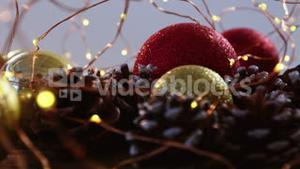Christmas bauble and pine cone arranged with christmas lights
