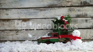 Toy car carrying fir with snowman
