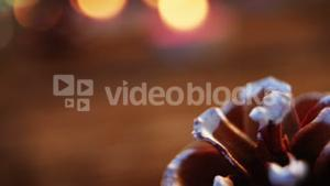 Pine cones with fake snow on wooden plank