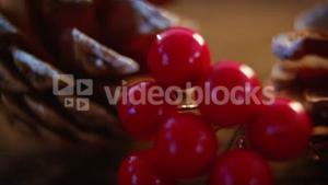 Pine cones with fake snow and cherry on wooden plank
