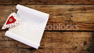 Heart and blank paper on wooden plank