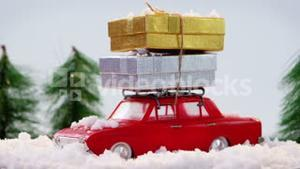 Toy car carrying christmas present with fake snow