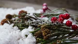 Pine cone and red cherries with fake snow