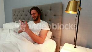 Young man using mobile phone in bed