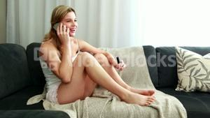 Woman applying a nail polish and answering call in living room