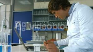 Scientist checking prescription and using laptop