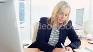 Businesswoman using computer and taking notes