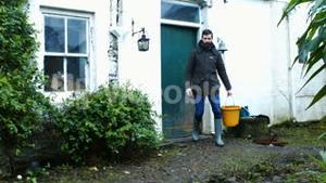 Man walking out of door and carrying bucket of water