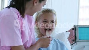 Nurse checking a little girls throat in hospital
