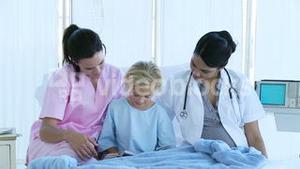 Little girl reading with a nurse and a doctor in bed