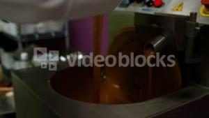 Worker pouring melting chocolate in blending machine