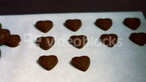 Worker arranging heart shaped dark chocolate on tray