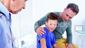 Male doctor treating patients hand