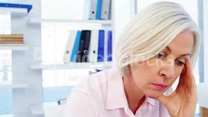 Stressed female doctor sitting at her desk