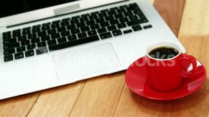 Close-up of laptop with coffee cup