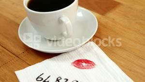 Close-up of coffee cup with lipstick mark and message written on tissue