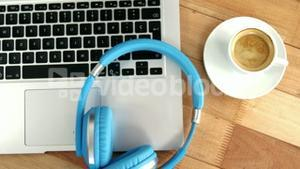 Cup of coffee with laptop and headphones