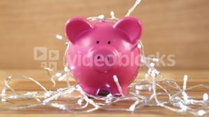 Piggy bank with fairy lights on wooden table