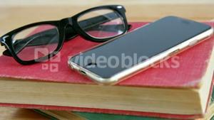 Mobile phone with spectacles and book