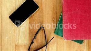Mobile phone with spectacles and books