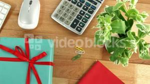 Calculator, gift box, diary, pot plant, pen and cup of coffee