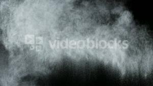 White dust powder blowing against black background