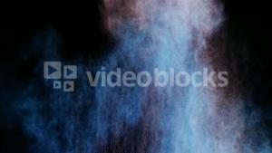 Blue and red dust powder blowing against black background