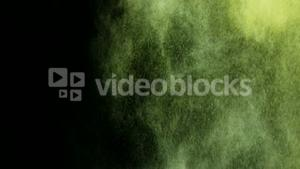 Green and yellow dust powder blowing against black background