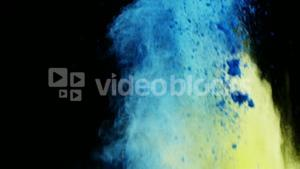 Blue and yellow dust powder blowing against black background