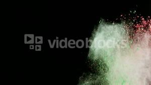 Green and red dust powder blowing against black background