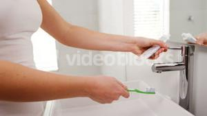 Mid section of woman washing toothbrush under sink in bathroom