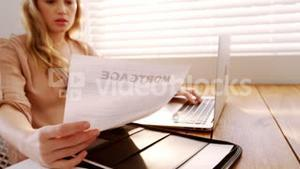 Woman looking at bill while using laptop