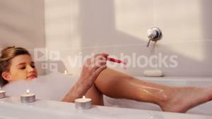 Woman using razor while having bath in bath tub