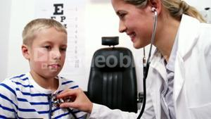 Female doctor examining young patient with a stethoscope