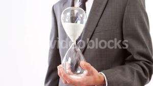 Businessman holding sandglass against white background