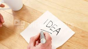 Man having a cup of black coffee while writing on piece of paper
