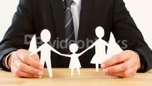 Businessman holding a paper cut out of family