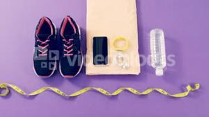 Mobile phone with headphones, shoes, water bottle, fitness band, exercise mat and measuring tape