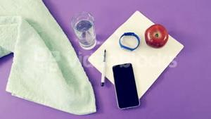 Mobile phone, napkin, water, apple, notebook, pen and fitness band