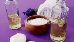 Sea salt in wooden bowl, towel, oil, candle and flowers