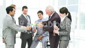 Senior manager and his business team celebrating Christmas in office with champagne