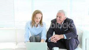 Businesswoman and senior businessman working with a laptop